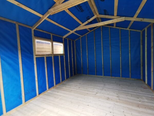 Inside the taller wooden shed, showing a high apex roof. The walls are lined with a blue fabric and the supporting panels are bare. There are 2 windows to the left hand side of the shed, through which you can see another wooden shed's wall.