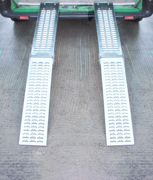 Two Folding Ramps lined up and raised to the back of a green van. The ground below is slick and wet looking and it reflects