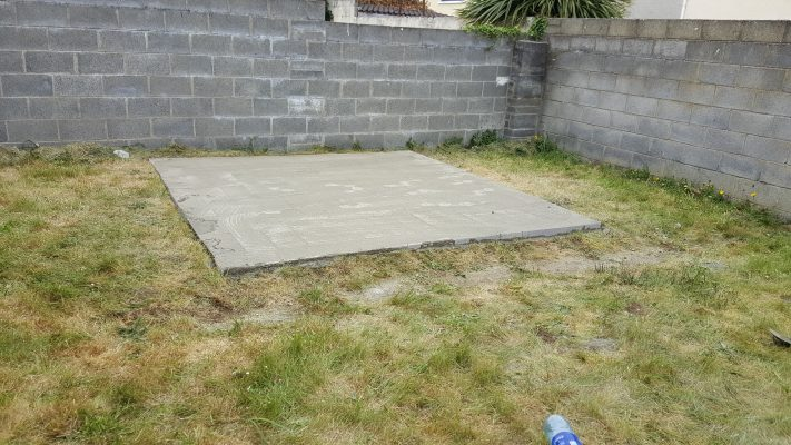 A solid, level concrete base with grass around it. The base is raised and it's perfect to put a shed on.