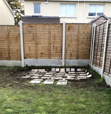 Paving Slabs laid out on a sloped batch of grass. The paving slabs are not connected together, they are both raised above and sunk into the grass and some are at an almost 45 degree angle on the bank of the back wall of the garden.