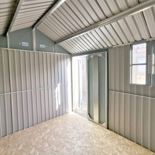Inside the 10ft x 7.5ft steel cottage shed. The view is from the end opposite door. The doors are open the window is letting light flow in and the apex is visible too. The support frame beams are shiny metal and the walls are a matte-effect metal. The floor is a plywood.