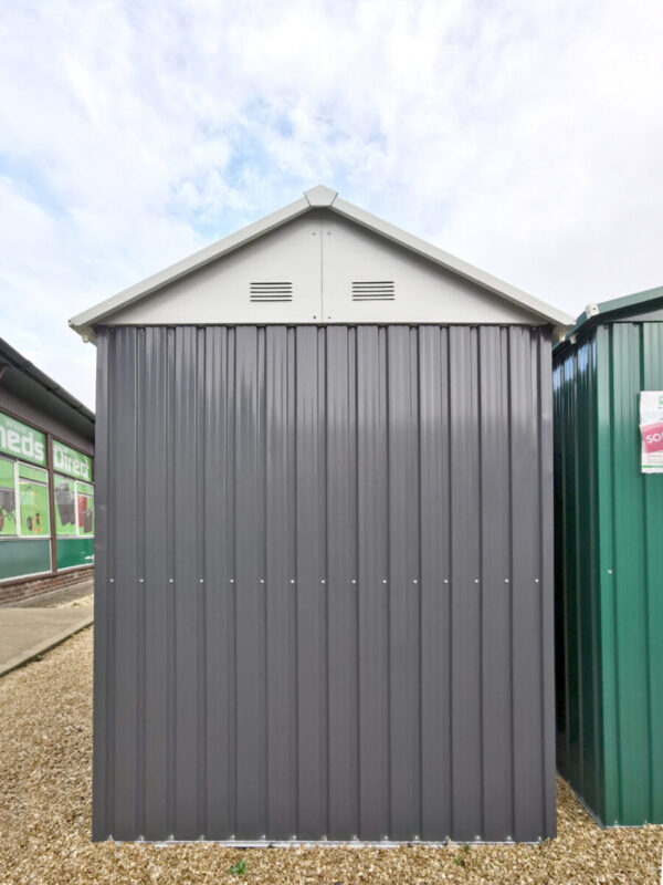 A view of the side of the shed, showing the peaked apex and vents