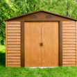 A woodgrain steel shed under a willow tree in a large garden. The shed is oak brown, with chocolate brown flashings around the door and vents. The shed is tall and wide and it casts a long shadow.