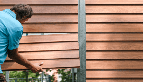 A man is placing the last row of 4 panels into place on the wood grain shed.