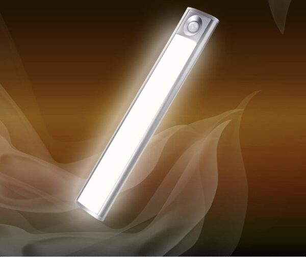 A long, silver LED Light at a 45 degree angle. It's illuminated and there is a golden swirl of smoke behind it.