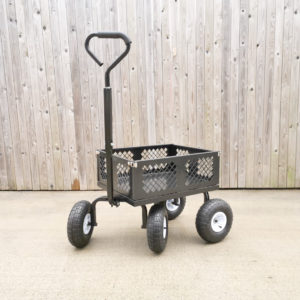 A black, metal box cart with silver hinges on each corner against a wooden backdrop. Its small, the wheels are almost as large as the box part of it. The hnalde is very large and wide too.