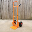 The Collapsible hand trolley from Sheds Direct Ireland at full height. It's orange with black trim