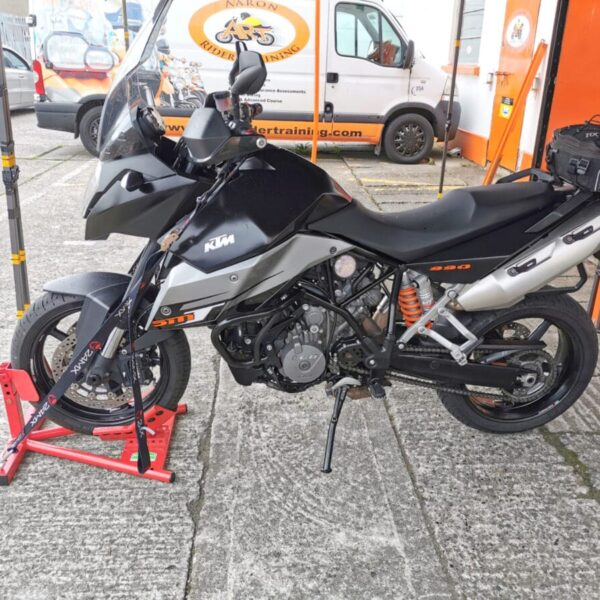 A side view of the motorbike on the stand. There are straps holding the bike in place and the bike stand is suspender, i.e. it is not touching the ground