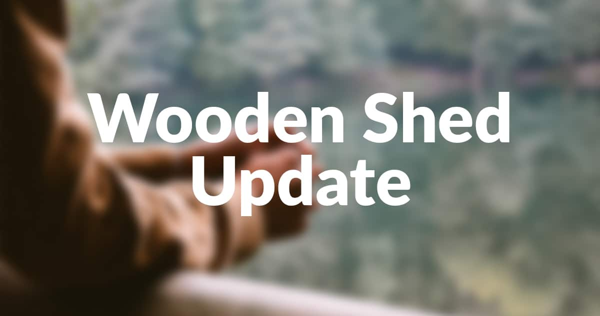 A picture of a pair of hands clasped together on the veranda of a wooden shed. The image is blurred and sharp letters sit on top that read 'Wooden Shed Update'