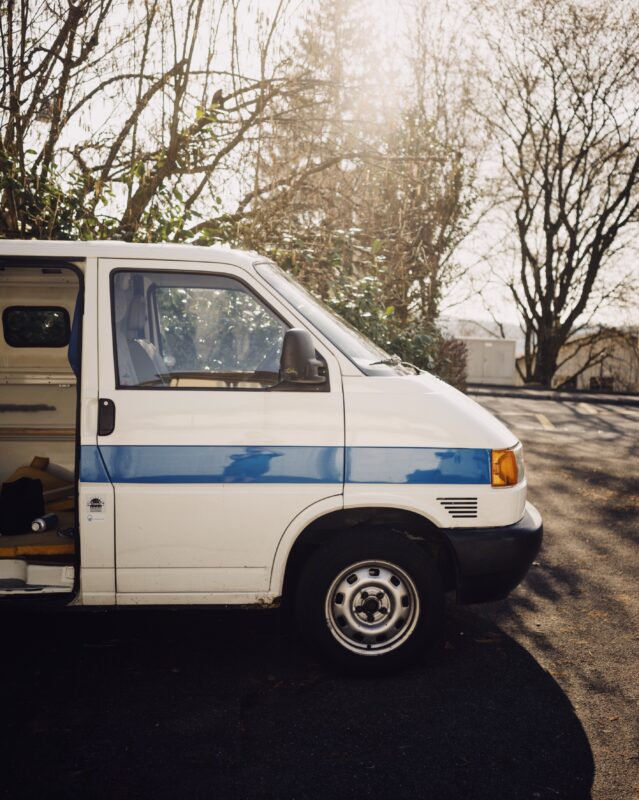 A white transport can with the door open is backlight by a warm wintery sky. The trees behind are bare and the van is empty of people. The van is white with a blue strip along the side.