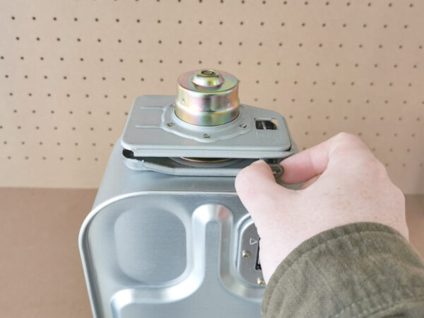 A white hand is reaching out to the button on the inverter cap and it is gripping the button with the thumb