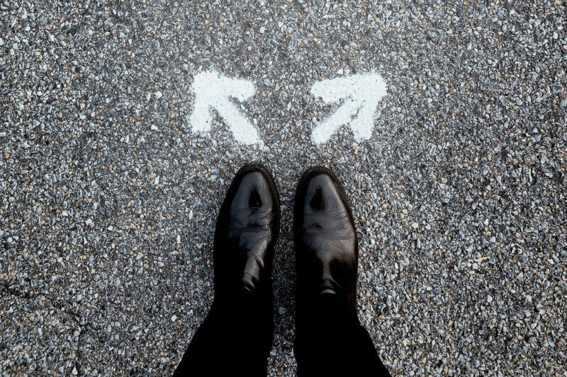 A pair of feet as seen from above. They are wearing black, leather formal shoes and black suit pants. In front of the shoes are two arrows in white spraypaint. One is pointing left and the other, right.