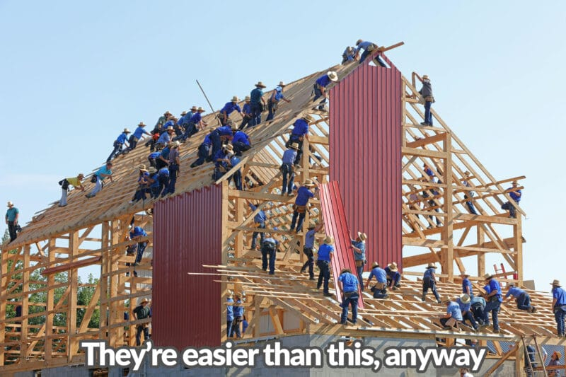 At least 40 Amish men in light blue shirts and dark blue pants are standing on an enormous shed structure, piecing it together. Some are holding wooden panels, others are holding pieces of paper and some and are hammering nails. It reads 'well, it's easier than this anyway'