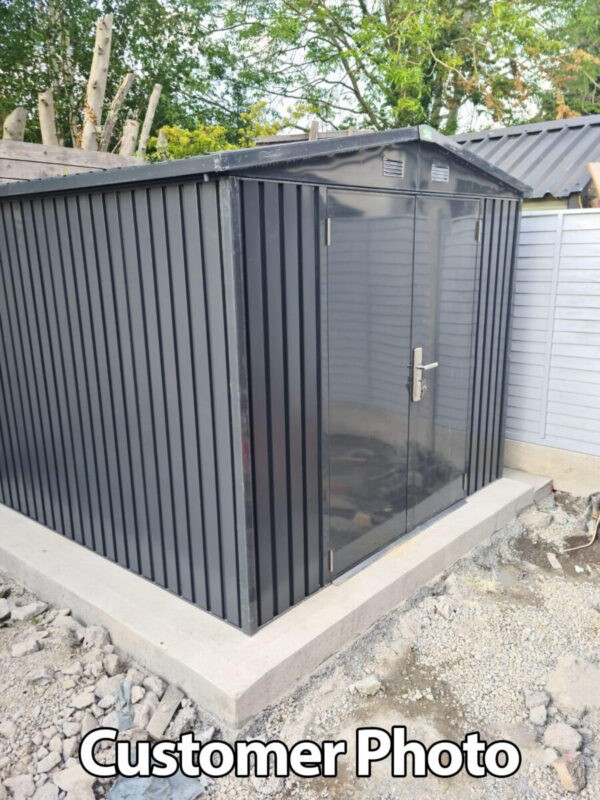 a customers photo of the 8ft x 10ft premium shed on a concrete slab. It is against a wooden panel wall and the ground around the slab is incomplete rubble