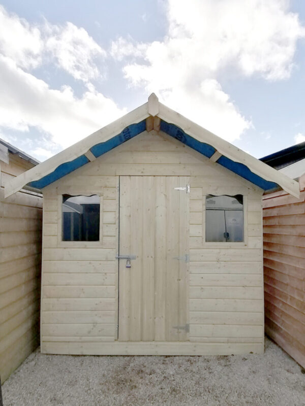 An exterior view of the Overhang wooden shed as seen in. aportrait orientation with lots of blue sky above the shed
