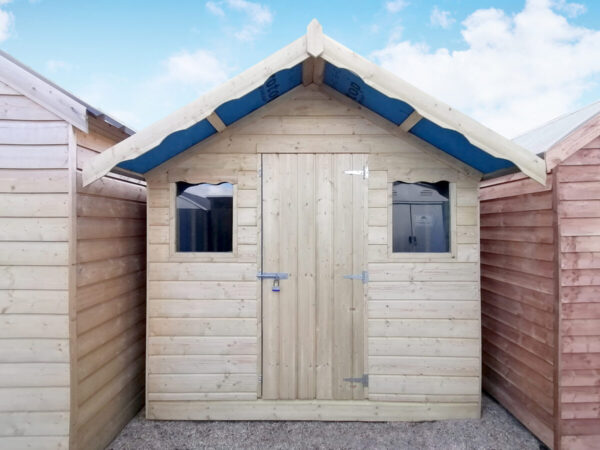 A front view of the Wooden Overhang Shed from Sheds Direct Ireland. This golden-wooden shed has a large, 2 foot protruding roof )i.e. the overhang) which casts a shadow over the top of the shed. There are two windows and a single door on the front of the shed.