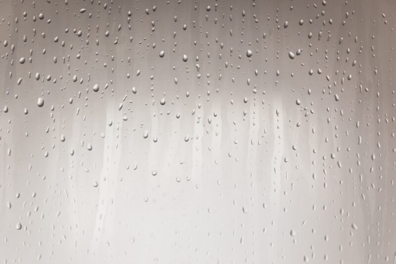 Condensation forming and water droplets running down a pane of glass