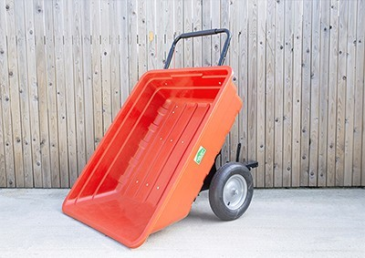 A large, red garden cart tipped down against a wooden wall