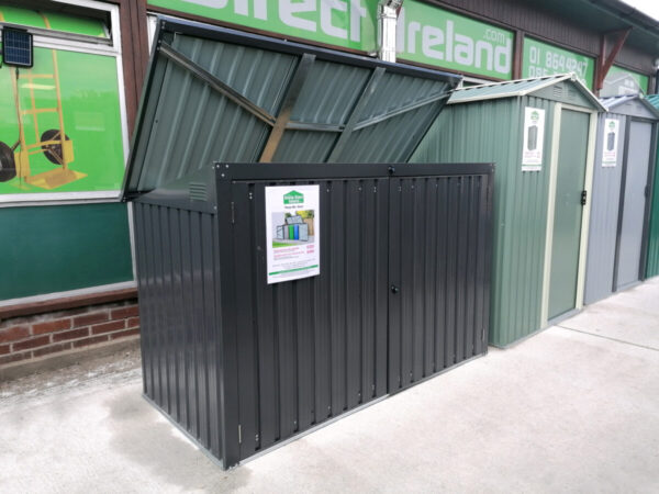 The bin store as seen from a 45 degree angle. The lid is open showing the paler grey colour that is on the inside. The unit itself is a dark grey and there is a white rectangular piece of paper on the front of it while denote the details of the shed to customers