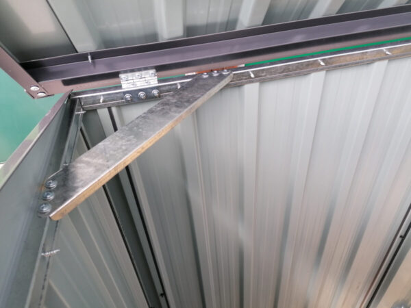 The internal brace bar of the 3-bin store. It's a shiny, silver colour and it creates a right angled triangle with the edges of the unit