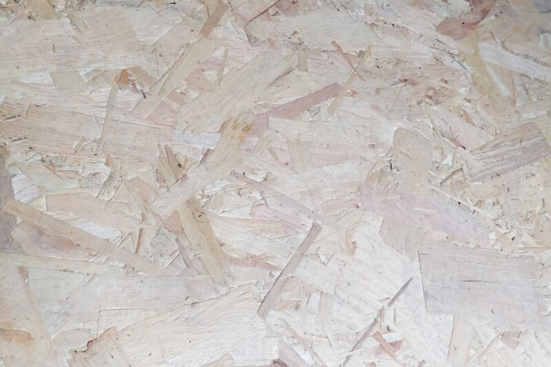 A close up view of OSB board, that shows the various strands of wood that have been pushed together to form the board