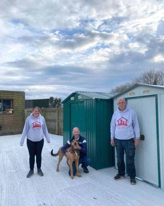 The team of Ramona and Chris from Coolronan Dog Rescue stand beside their new green and white sheds, while Alan from Sheds Direct Ireland hugs Hunter the dog.