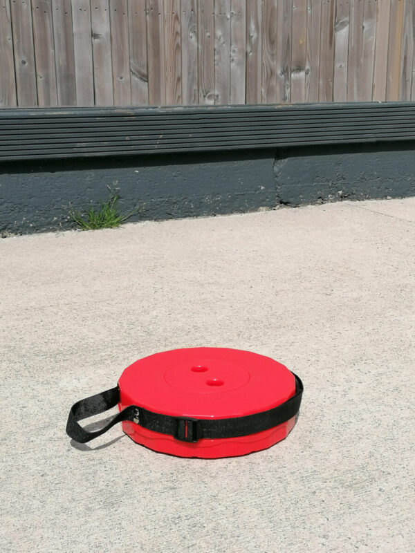 The red pop up stool in it's most compacted state. It is only 6cm tall and appears flat on a concrete ground below it. Behind there is a wooden fence.