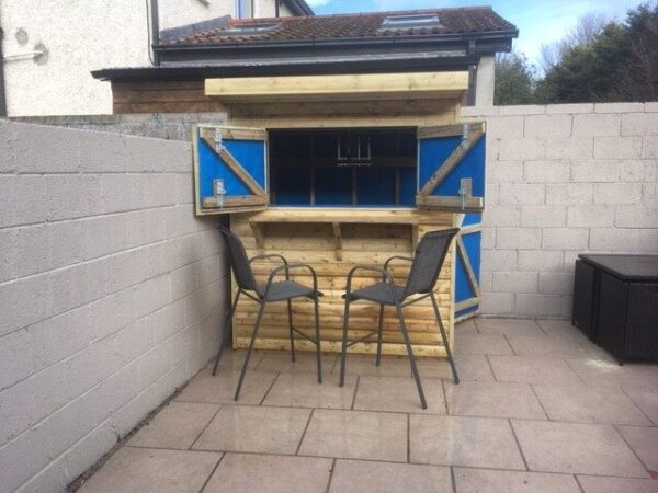 The Tolka Garden Bar from Sheds Direct Ireland in the corner of a garden. The windows are open showing the inside which is lined with blue material. There are two seats in front of the bar and a slate-grey wall behind it and to the left. There is a neighbours house visible behind it.