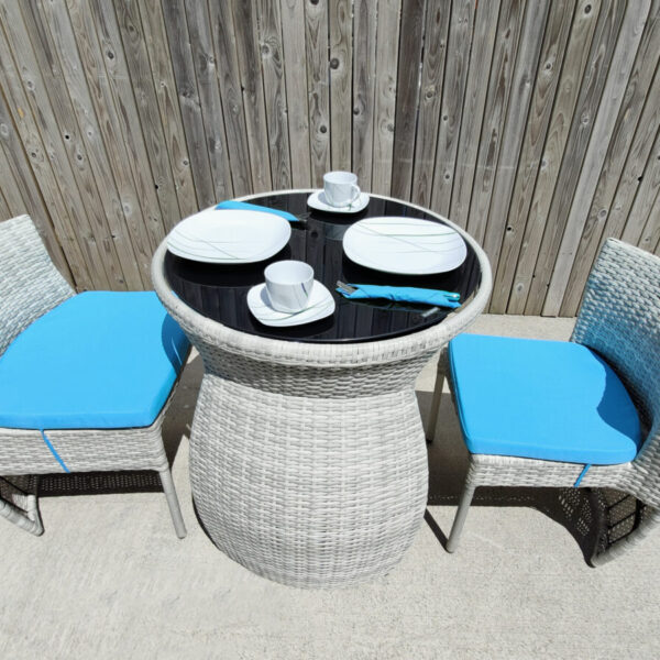 An aerial view of the fold in table and chairs set. There are bright blue cushions on the chairs, two large white plates and white cups and saucers on the table