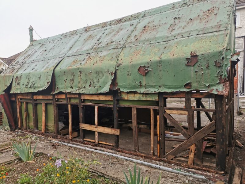 a battered old, green shed. The sheet metal on it is green and rested oragne and the supporting wooden frame is clearly visible through enormous holes in it