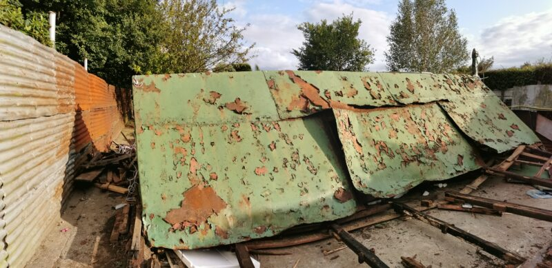 The rusted green shed in the previous image now crumped in a pile having being felled by a hurley.