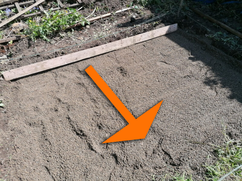 a relatively flat piece of gravel witha. large wooden plank sitting at the top of it. A super-imposed orange arrow shows the direction that it should be dragged