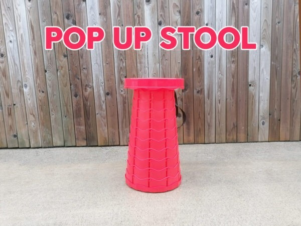 The red Pop Up Stool in front of a wooden fence. It is fully extended and above it the words 'pop up stool' are written in bright red text