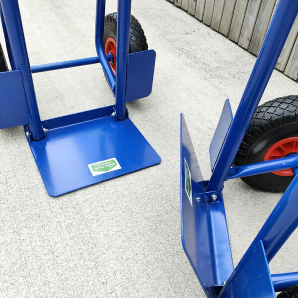 The folding footplate on the blue hand truck. Two trollies are side by side, one has the footplate down, the other has it up