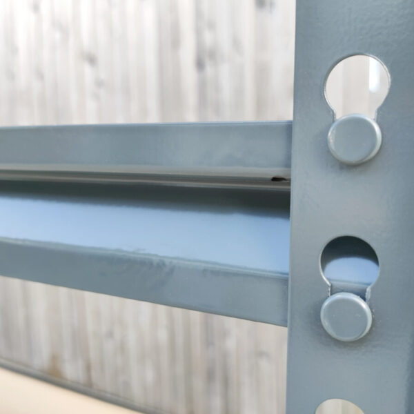 A close-up shot of the locking mechanism that keeps the shelves affixed to the frame. The port is shaped like the outline of the number 8 and the point that sits into this is circular. This allows it to enter at the top and slide into the bottom point securely.