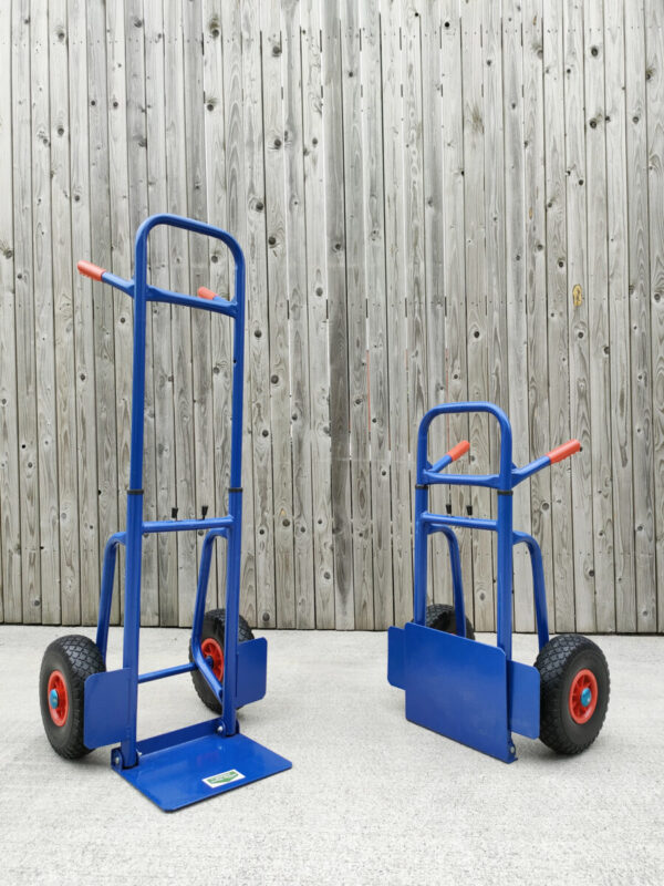 Two of the blue hand trucks with extendable backs side by side. The are both at 45 degree angles, pointing inwards towards the camera. The one on the left is fully extended. The one on the right is compacted.