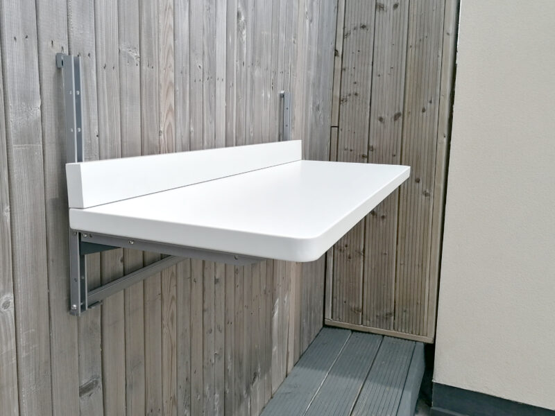 White Balcony table attached to a brown fence