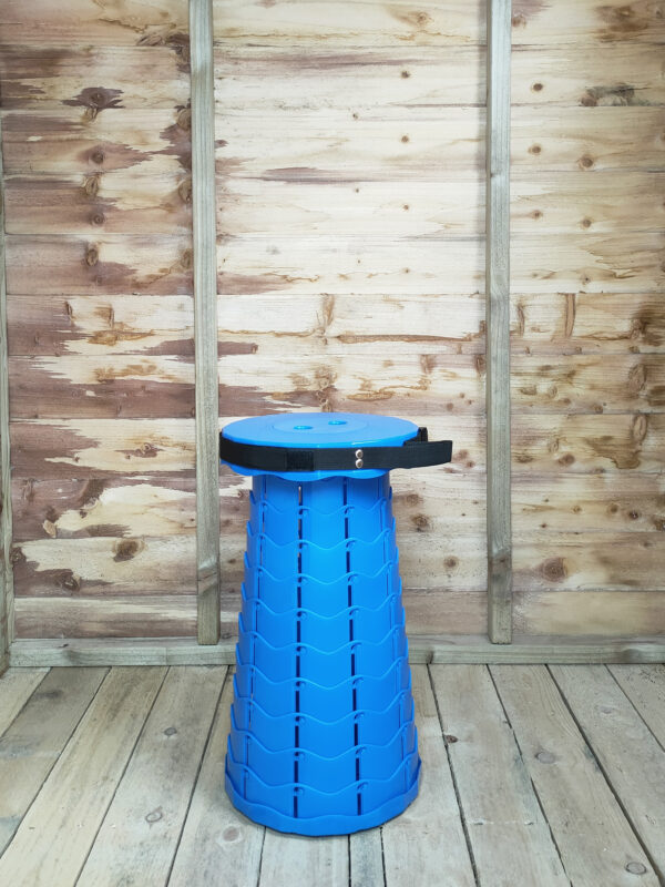 The Blue pop up stool in bright blue against the internal wooden wall of the rustic wooden shed