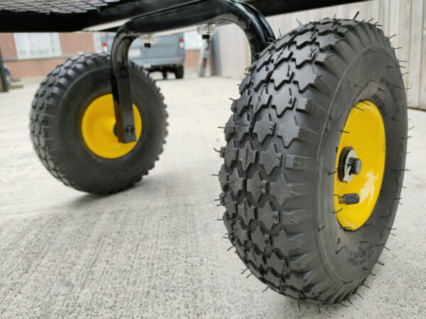A close up view of the thick tyres on the mesh cart. They are black rubber with an internal, bright yellow rim. They have thick grooves and they are 25cm in diamter and they are 8cm thick.