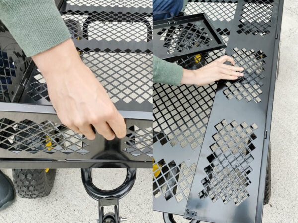 Two photos side by side. The first shows a mans hand lifting up the panel, the second shows it pulling it in towards his body to lay it flat down and to separate it from the body of the cart
