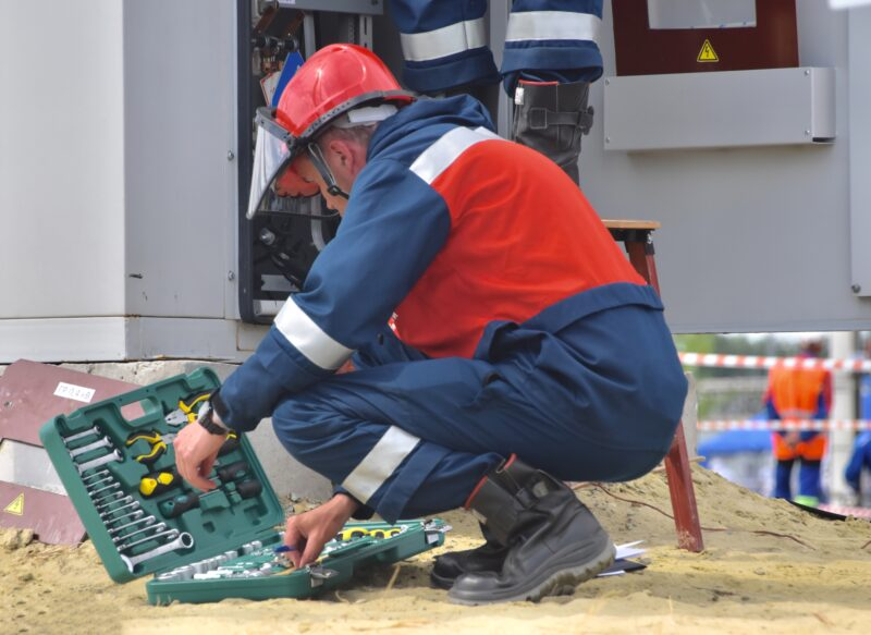 An electrician in a large red puffy jacket (who is not part of the steel shed assembly team), opening a box of electrical tools as he prepares to work