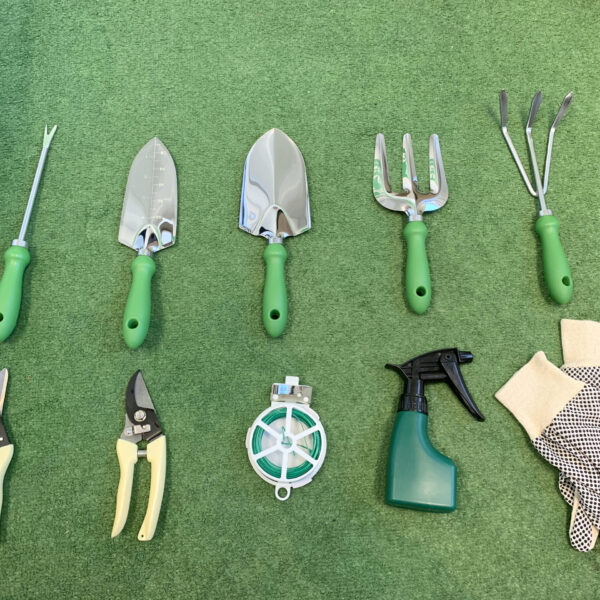 All the items from the garden tool bag with chair set laid out on a grassy surface. There is a long pronged fork, two trowels, two rakes, two clippers, a roll of twine, a spray-bottle and a set of gloves
