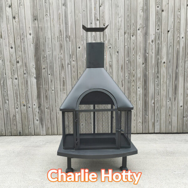 The Charlie Hotty Fire pit as seen face on from a relatively low height. It is a squat, square base fire-pit supported by 4 legs and it has a chimney above the fire pit.