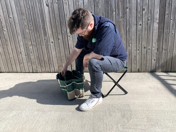 Sean from Sheds Direct Ireland sitting on the chair from the garden tool bag with chair set, reaching into the bag pulling out a trowel
