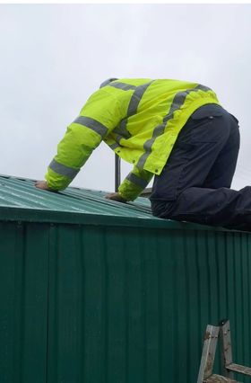 A man in a hi-vis jacket kneeling on the edge of an assembled, green shed. He has both hands on the shed