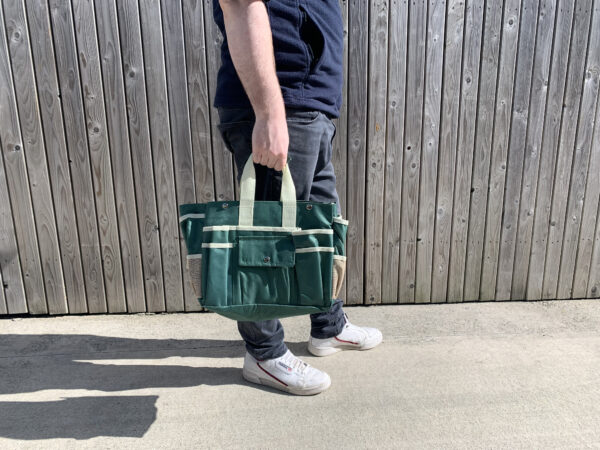 A man in a navy jumper holding the bag from the set