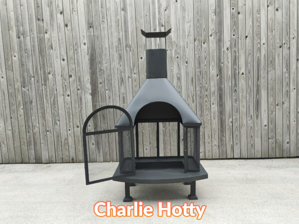 The charlie hotty fire pit asseen with the grate door open. It is a large, squat, black firepit against a wooden wall