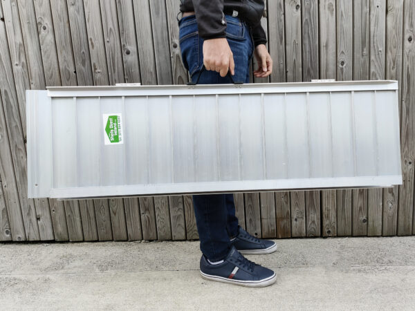 The Medium Wheelchair Ramp being held by a man in a navy shirt, dark jeans and navy shoes. He is holding the ramp in one hand. It looks heavier in his arms than the small, but he still seems relatively unphased.