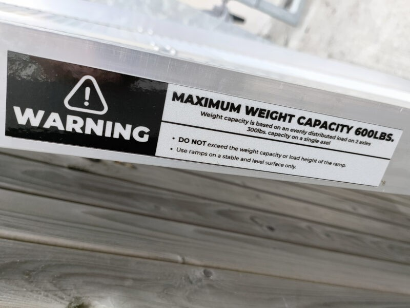 The warning sticker on the side of the ramp. It reads: MAXIMUM WEIGHT CAPACITY 600LBS. Weight capacity is based on an evenly distributed load on 2 axles. 300lbs capacity on a single axel. Do not exceed the weight capacity or load height of the ramp. Use ramps on a stable and level surface only'