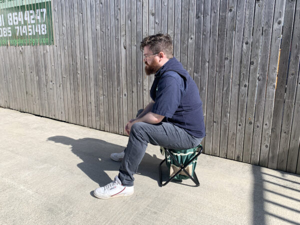 Sean from Sheds Direct Ireland sitting on the chair from the garden tool bag with chair set